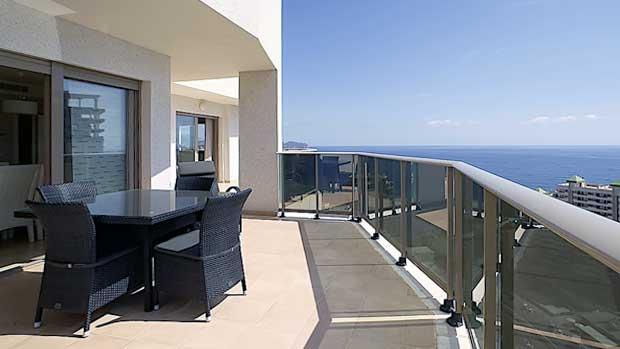 Открытая терраса с обеденной зоной элитных апартаментов в Кальпе в высотном жилом комплексе на побережье Коста-Бланка в Испании