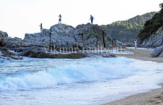 Cкальный массив на пляже Playa de Sa Boadella на фоне мыса Punta de s'Aguia в Ллорет де Мар