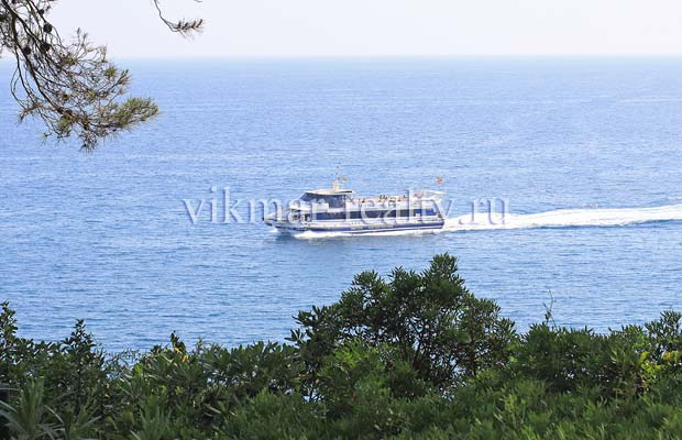 Экскурсионное судно на фоне акватории бухты Cala Boadella в Ллорет де Мар